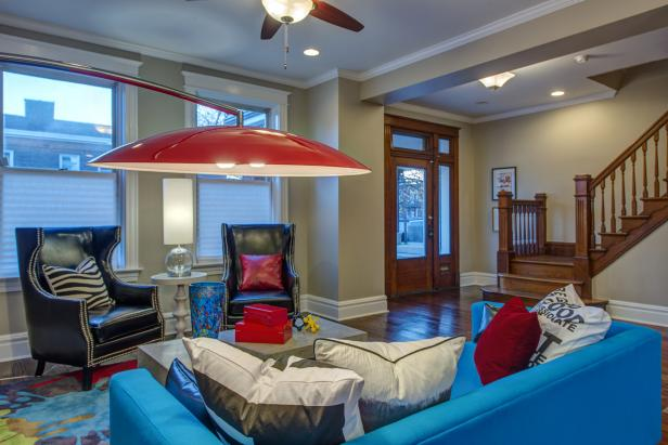 Eclectic Living Space With Blue Sofa, Red Lamp & Black Chairs