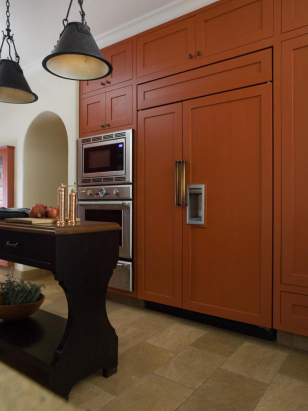 White Kitchen With Orange Cabinets & Wrought Iron Pendants