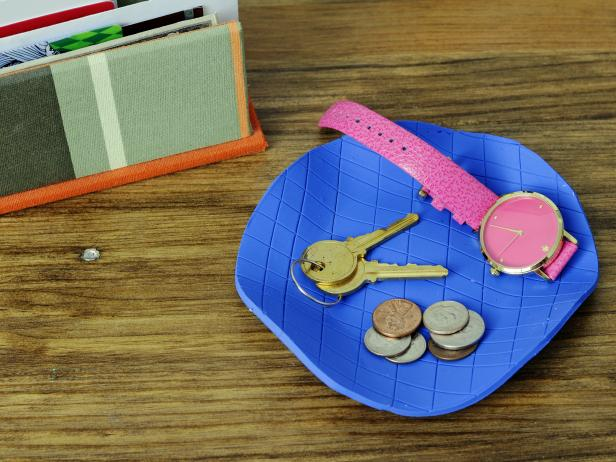 Roll out bakeable clay and add a pattern with basic household items, like a pencil eraser or a piece of lace. Bake and fill with jewelry, keys or other household items.