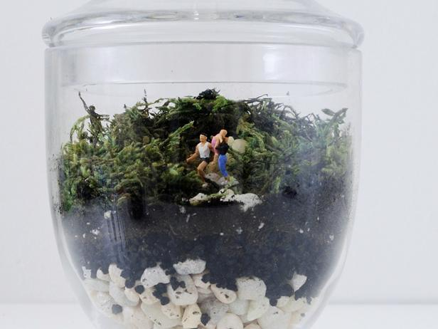 Terrariums are one of the easiest ways to keep plants alive in your home. Make one with a tiny family inside using miniature train display figures.