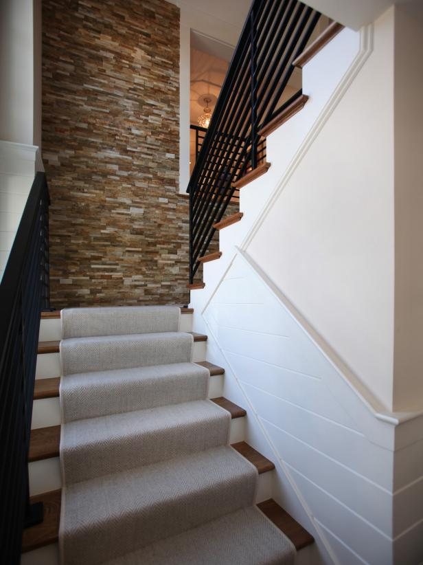 Neutral Staircase With Stone Wall and Beige Carpet Runner