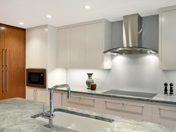 Kitchen With White Cabinets, Gray Countertops and Stainless Steel Hood