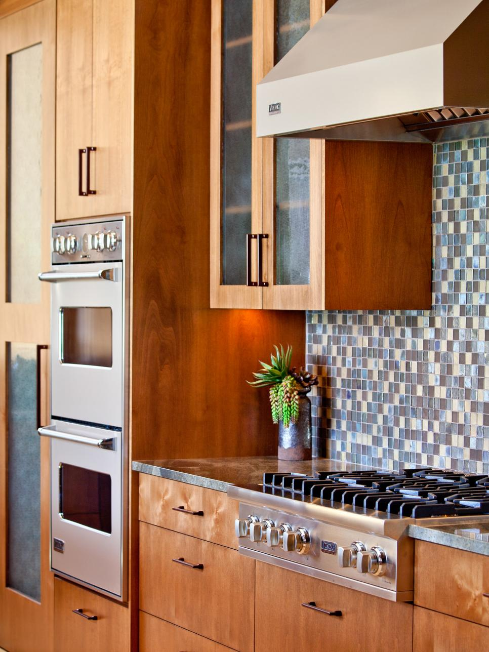 Kitchen With Wood Cabinetry, Mosaic Tile Backsplash and Built-In Appliances