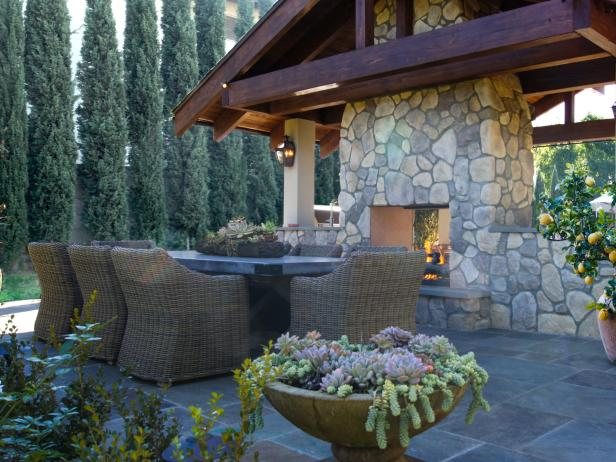 Outdoor Dining Area with Stone Fireplace and Lush Landscaping