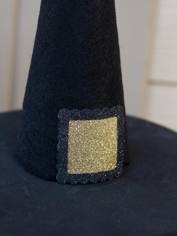 As a finishing touch, create a buckle by placing a small square of gold glitter paper behind a small picture frame sticker, securing them both to the hat with hot glue.