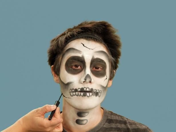 Complete your Halloween skeleton look with details. To add character to your skull, create a few cracks in the bone using liquid eyeliner. Add uneven lines at the forehead, on the cheek and chin