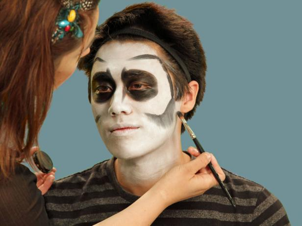 Add bony contours to skeleton makeup by using a flat craft brush to apply black cream makeup to outline the bottom of the cheekbone. Take the line close to the hairline and all the way up to the forehead, almost to the middle and about an inch over the eyebrows. Starting with the cheek, carefully use the brush to blend the line downward to create the look of a shadow. Use small moves until you get the hang of blending and, if necessary, use a makeup sponge to soften any harsh lines. Then, blend the top line down as well.