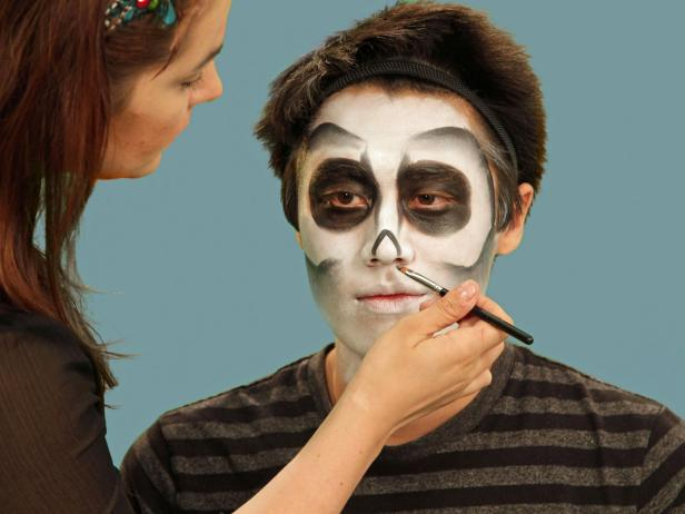 Use a small brush to draw the skeleton nose. Draw a triangle just over the tip of the nose and blend downward, making certain to leave the very tip of the nose white.