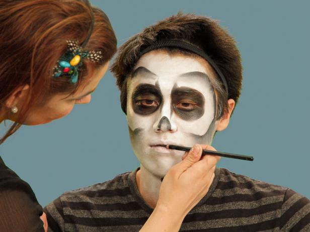 To make a mouth full of ghoulish teeth, use a black eyeliner pencil to line where the lips meet. Extend the natural lip line about two inches from the mouth on each side.