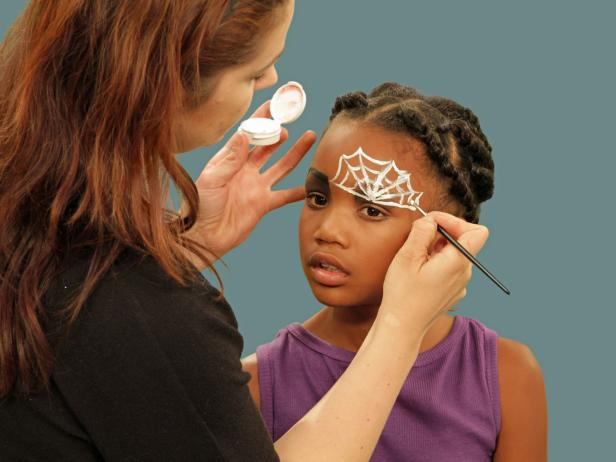 Make a spider web eye for fun Halloween spider makeup. On one eye, create a spider web. Using white face paint and a thin craft brush, start just above the crease in the eyelid and draw lines up and outward. Connect them with one line that dips down between each point.