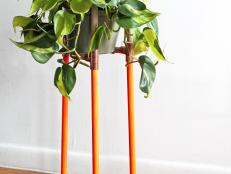 A fresh take on a plant stand using materials found in your local hardware store, this wood and brass plant stand can be adjusted to fit any size planter. A few coats of neon paint give it a modern edge.
