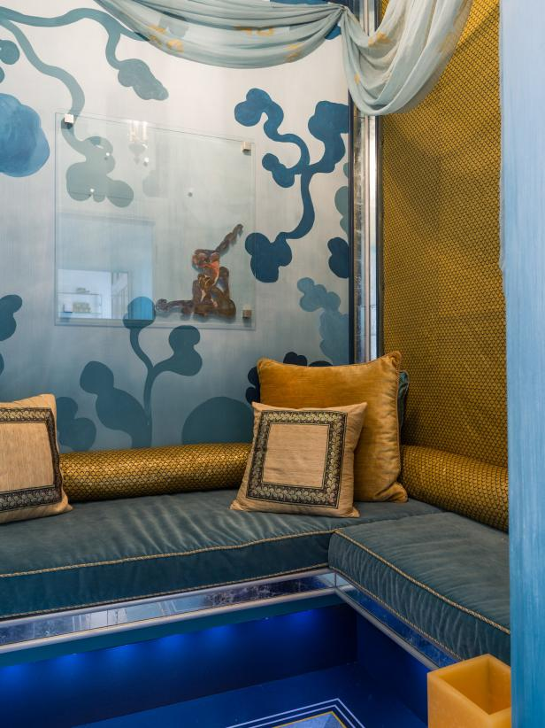 Bench Seating With Blue Cushions and Gold Pillows and Fabric Walls