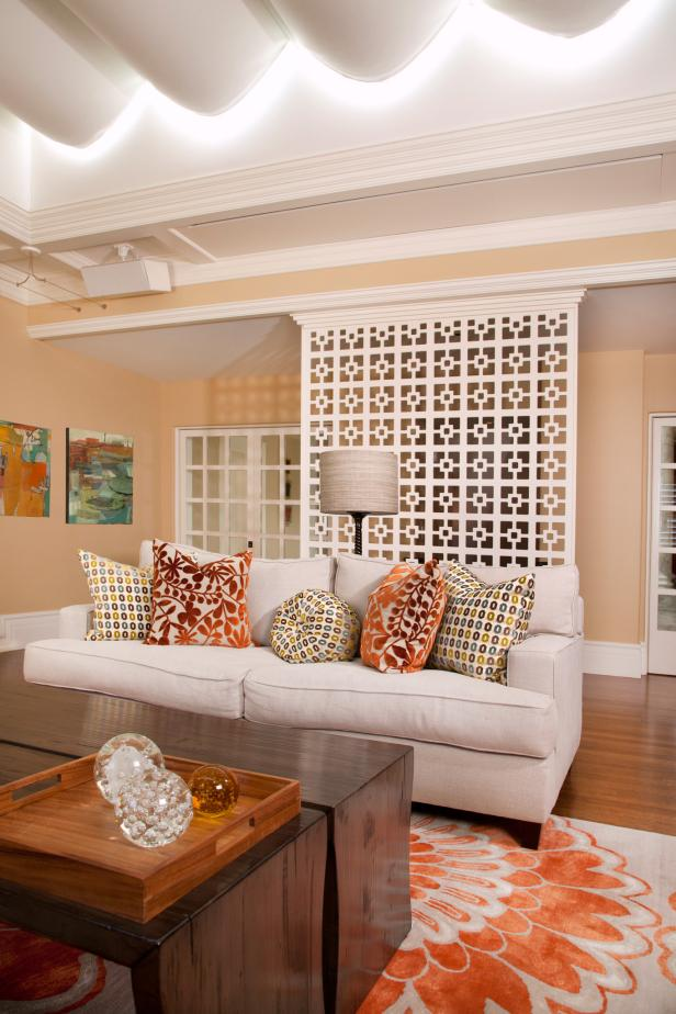 Living Room With White Screen, Sofa, and Orange Floral Rug and Pillows