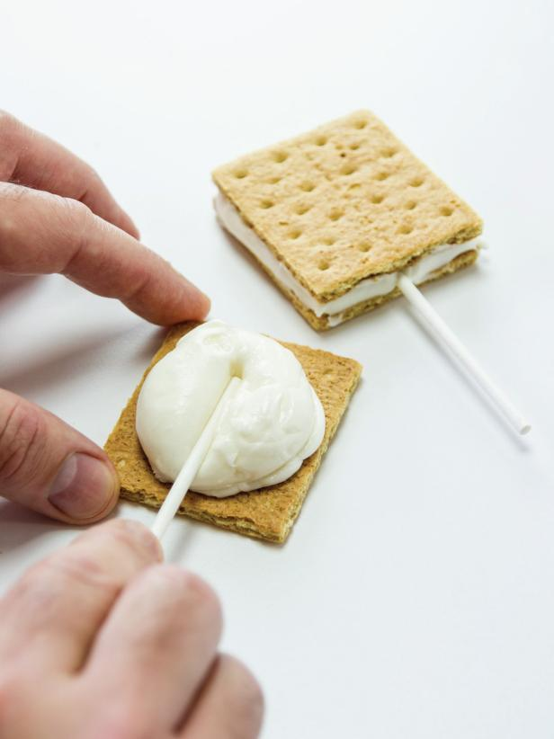 Place a lollipop stick in the middle of the marshmallow filling with the top of the stick about an inch from the bottom edge of the graham cracker.