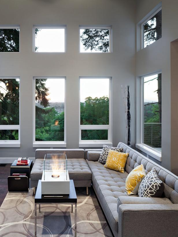 A low-backed modern gray sectional makes room for the views to be enjoyed from all angles. Patterned throw pillows and rug add depth and color to the design. The modern coffee table features a white built-in fire pit.