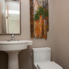 Gray Bathroom With Pedestal Sink and Rustic Wall Art