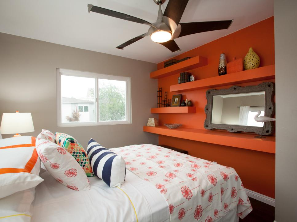 Bedroom With Colorful Bedding, Orange Storage Wall and Framed Mirror
