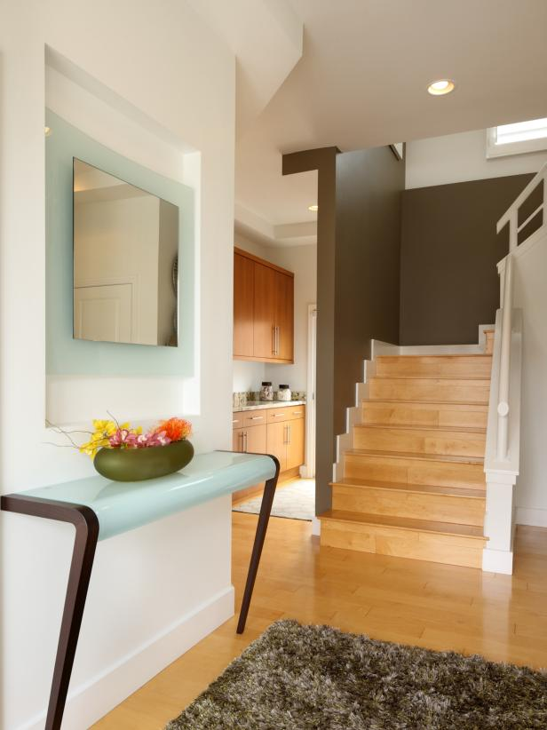 Entryway With Blonde Wood Floors, Blue Table and Frosted-Glass Mirror