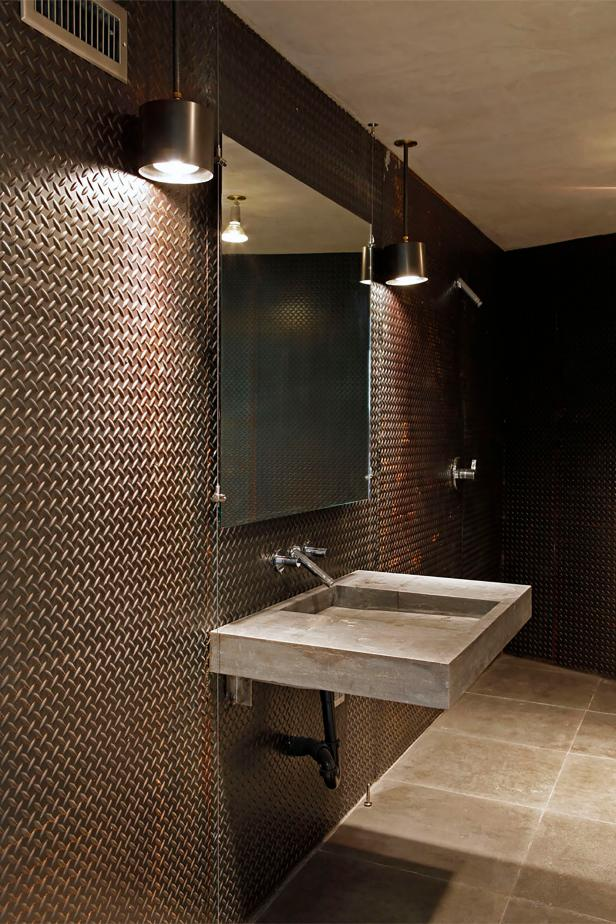 Bathroom With Metal Walls and Cement Floating Sink