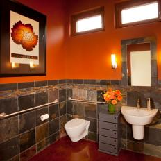 Modern Orange Bathroom With Dark Marble Half Wall and Floating Sink and Toilet