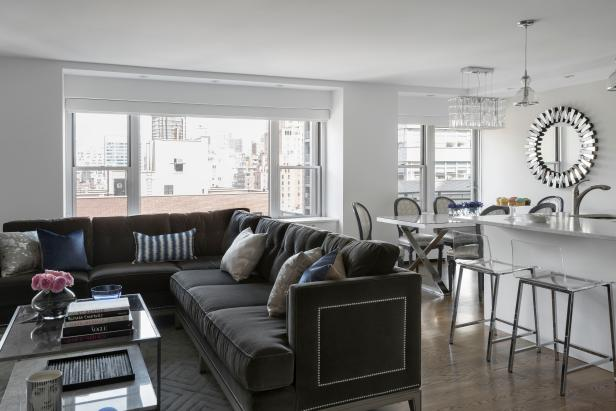 This posh apartment features an all-over white palette with gray accents, as seen in the plush gray sectional sofa with beautiful nailhead detailing on the back. The open floor plan allows for easy transition between the living, dining and kitchen areas, while lucite, crystal and reflective surfaces complete the look of the home.