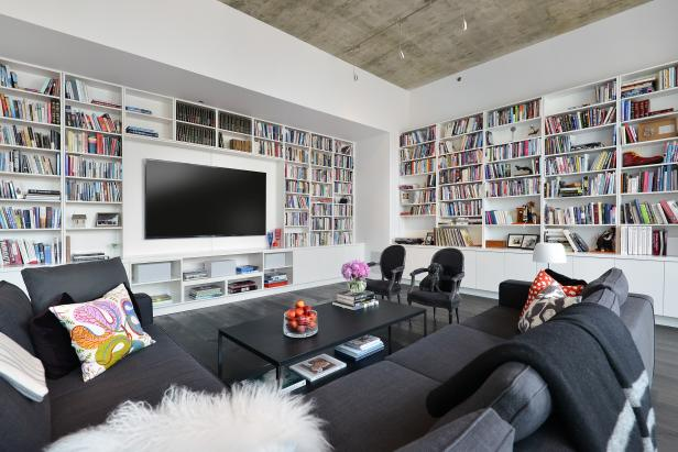 Wall-to-wall bookshelves form the backdrop for this enormous living room. A gray sectional provides a cozy spot for curling up with a book or watching a movie below the industrial concrete ceiling.