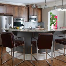 Transitional Kitchen Featuring Wood Cabinets, Red-Brown Leather Bar Stools and Cone Pendant Lights