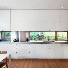 Modern White Laminate Kitchen Cabinetry Separated By a Long Window Backsplash and Stainless Steel Countertop