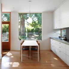 Sunny, Modern Eat In Kitchen White Dining Table Under Large Window, White Laminate Cabinets and Wood Dining Chairs
