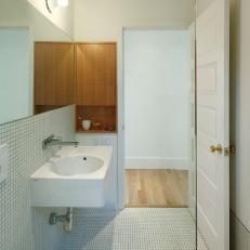 Minimalist Asian Bathroom With White Small Tile Floor and Half Wall, White Floating Sink and Wood Cabinet