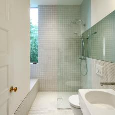 Modern Bathroom With Small White Tile, Glass Wall Shower Divider and Floating White Sink and Toilet