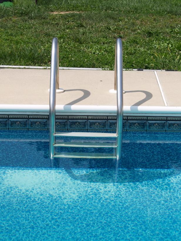 Pool ladder and ornamental tile around in-ground pool