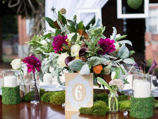 "To keep a wedding design cohesive, Kim Lettier, of Lettier Event Planning Studio, carries some elements of the focal point (here, it's a floral centerpiece) into other areas. ""Accent pieces such as candles should complement the focal point but not compete with it,"" she adds. ""The design of the vessel itself should also fit in with the overall look. In this case I wrapped moss around the vessels because its traditional look interfered with the organic and vintage feel of the design."" Florist: The Green Flamingo."