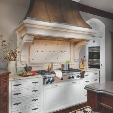 Traditional Kitchen With White Cabinets and Dramatic Range Hood