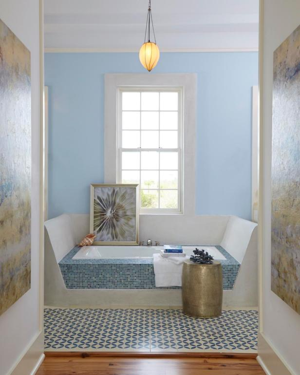 Light Blue Bathroom With Tile Soaking Tub and White Window