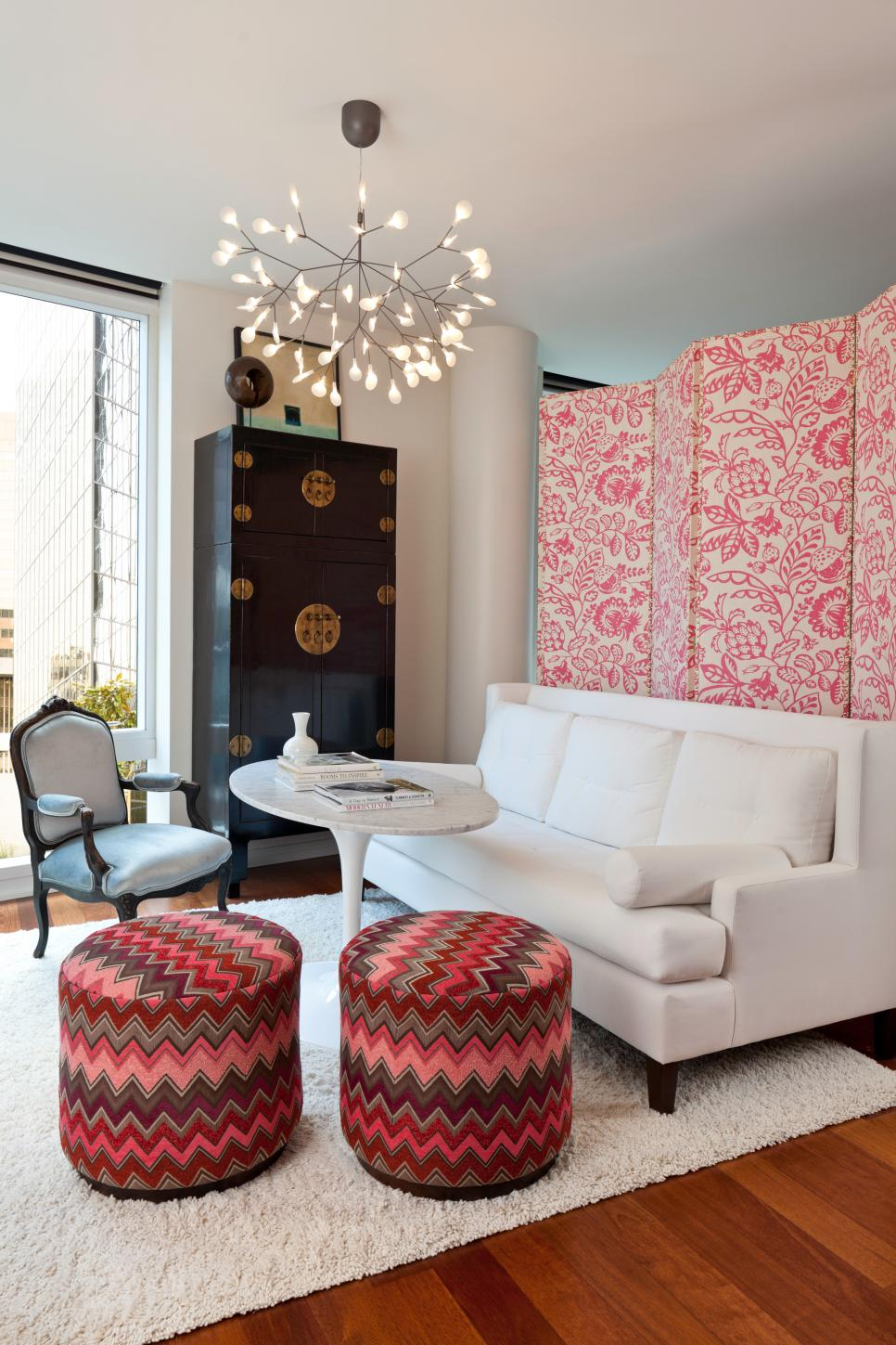 Living Room With Pink Floral Partition, White Sofa and Chevron Stools