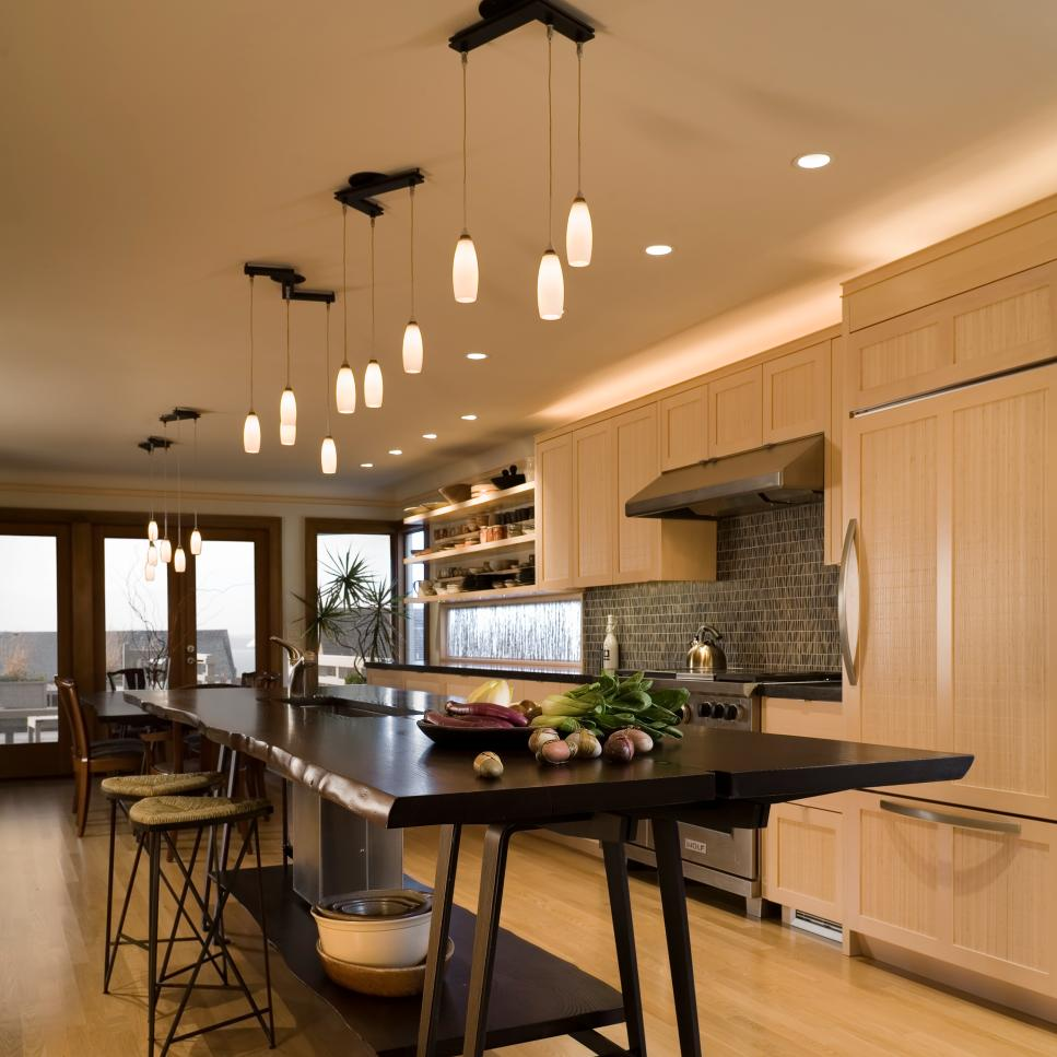 Neutral Kitchen With Pale Wood Cabinets, Dark Island, Pendant Lights