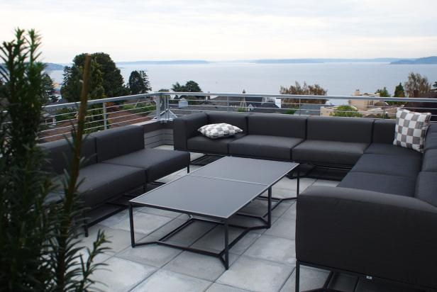 Contemporary Concrete Patio With Black Furniture and Metal Railing