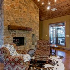 Rustic Living Room With Large Stone Fireplace, Animal Hide Rug and Plush Armchairs