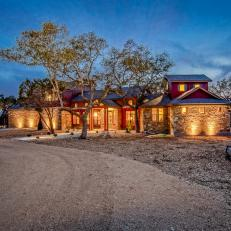 Beautiful Home Exterior With Warm Outdoor Lighting & Mulched Yard