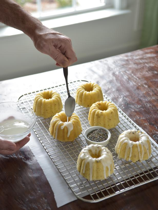 Use a small spoon to drizzle glaze from the small bowl and onto the cooled cakes.