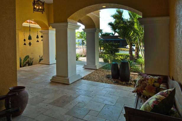 Covered Tile Patio With Yellow Stucco Walls and White Columns