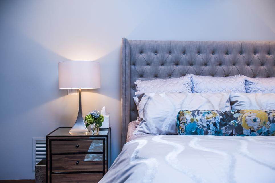 Bedroom With Gray Upholstered Headboard and Floral Pillow