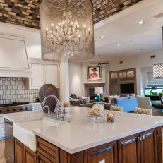 Dazzling Chandelier Above Wood Island in White Kitchen