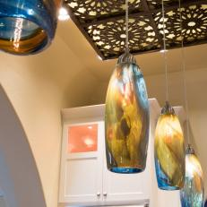 Swirled Blue And Yellow Pendant Lights Hang From Decorative Ceiling Panel