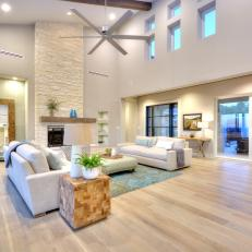 Open, Contemporary Living Room With Light Hardwood Floors And Tall Stone  Fireplace