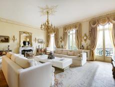 Lavish Victorian Living Room in Paris With White Furniture, Heavy Drapery and Gold Decorative Details
