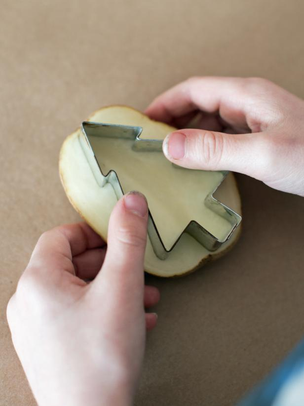 Press metal cookie cutter into the potato and cut around the cookie cutter.