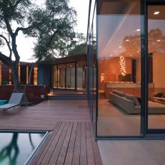 Modern Glass Home With Wood Back Deck and Ground-Level Pool