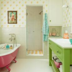 Yellow Patterned Tile and Wallpaper with Pink Bathtub and Green Vanity in Bathroom